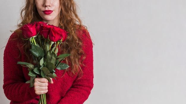 Linda mulher segurando um buquê de rosas