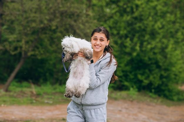 Linda mulher segurando um cachorro nos braços