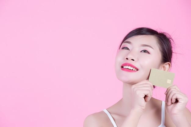 Linda mulher segurando um cartão em um fundo rosa.