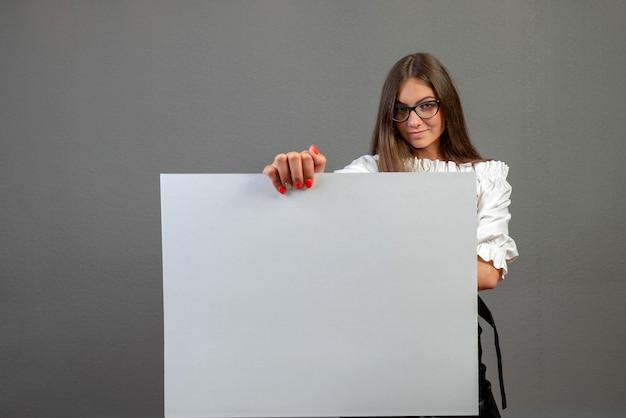 Linda mulher segurando um cartaz em branco, isolado no fundo cinza