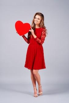 Linda mulher segurando um grande coração vermelho