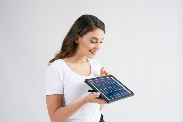Linda mulher segurando um modelo de painel solar