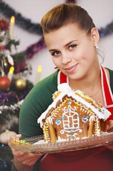 Linda mulher segurando um prato com casa de gengibre