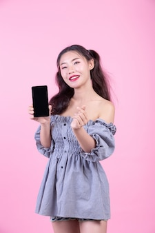 Linda mulher segurando um smartphone em um fundo rosa.