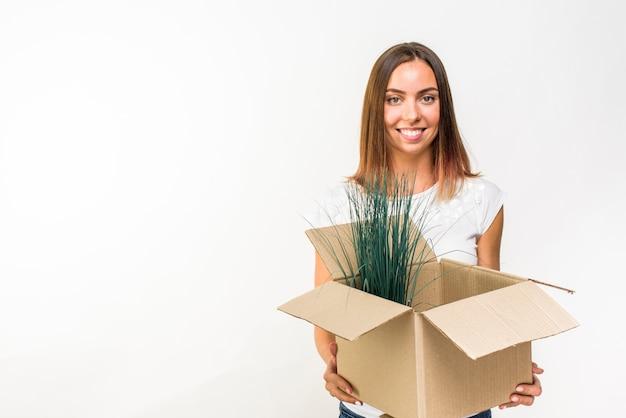 Linda mulher segurando uma caixa com uma planta
