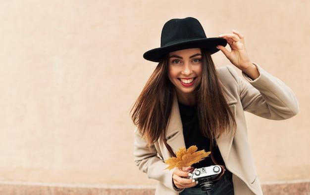 Linda mulher segurando uma câmera e uma folha