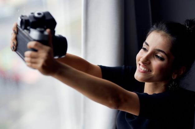 Linda mulher segurando uma câmera perto da janela decoração moda modelo