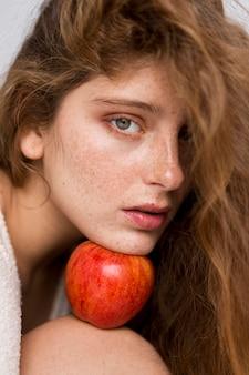 Linda mulher segurando uma maçã vermelha entre o rosto e o joelho