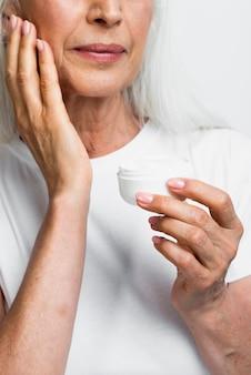 Linda mulher sênior aplicando cuidados com a pele