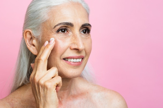 Linda mulher sênior aplicando tratamento de pele