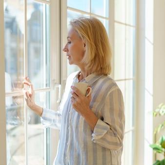 Linda mulher sênior com uma xícara de café, olhando pela janela, enquanto aproveita o novo dia em casa