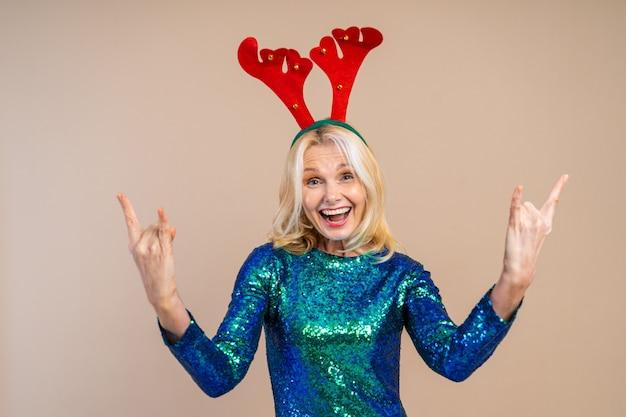 Linda mulher sênior com vestido festivo elegante se divertindo em uma festa