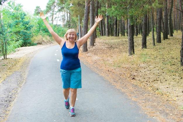 Linda mulher sênior correndo ao ar livre no parque.