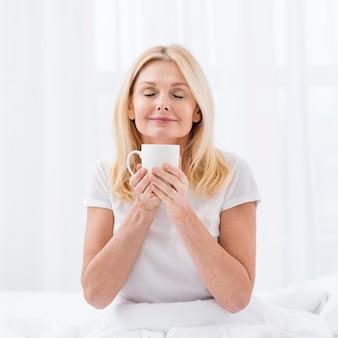 Linda mulher sênior desfrutando de uma xícara de café