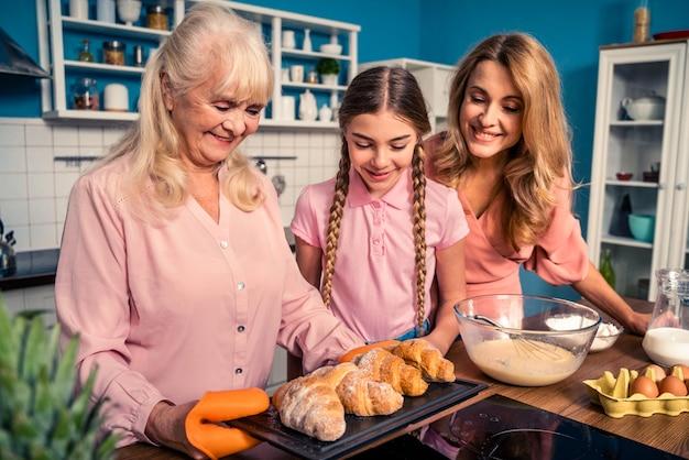 Linda mulher sênior e família trabalhando na cozinha