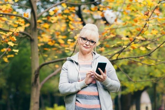 Linda mulher sênior em uma mochila, passeando no parque, falando ao telefone