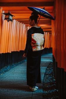 Linda mulher sênior japonesa andando no santuário de fushimi inari em kyoto