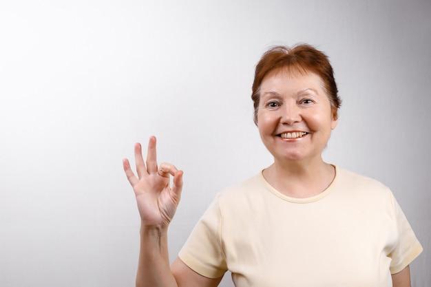 Linda mulher sênior mostra bem em branco em uma camiseta leve.