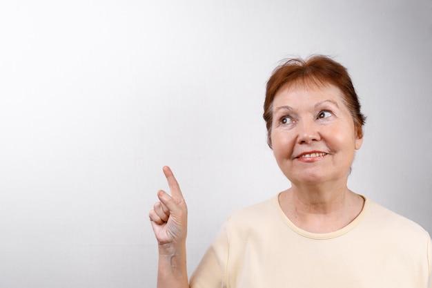 Linda mulher sênior mostra uma mão para o lado em branco em uma camiseta leve