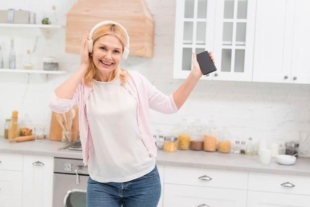 Linda mulher sênior ouvindo música em casa
