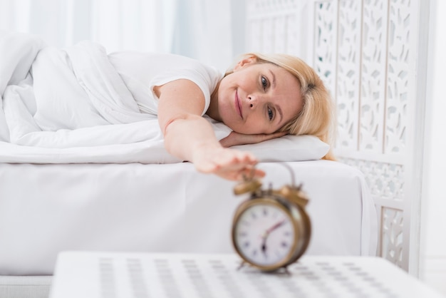Linda mulher sênior parando o alarme
