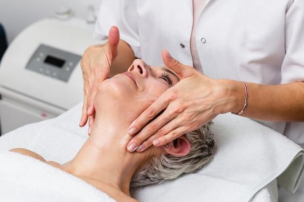 Linda mulher sênior, recebendo tratamento de massagem de spa no salão de beleza spa. tratamento de beleza facial.