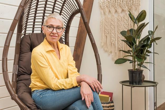 Linda mulher sênior, sentado em uma cadeira de madeira