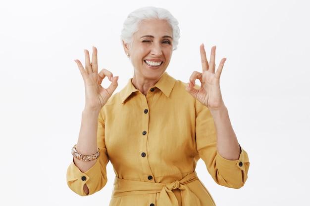 Linda mulher sênior sorridente mostrando um gesto de aprovação, aprovo e gosto da ideia, recomendo o produto