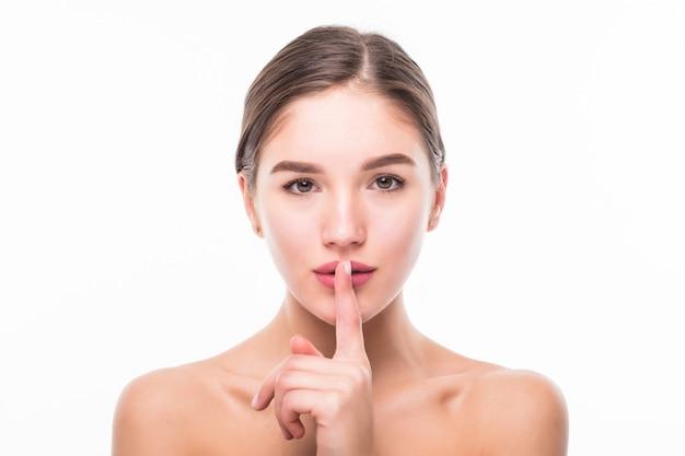 Linda mulher sensual dizendo shh com o dedo nos lábios, isolado na parede branca