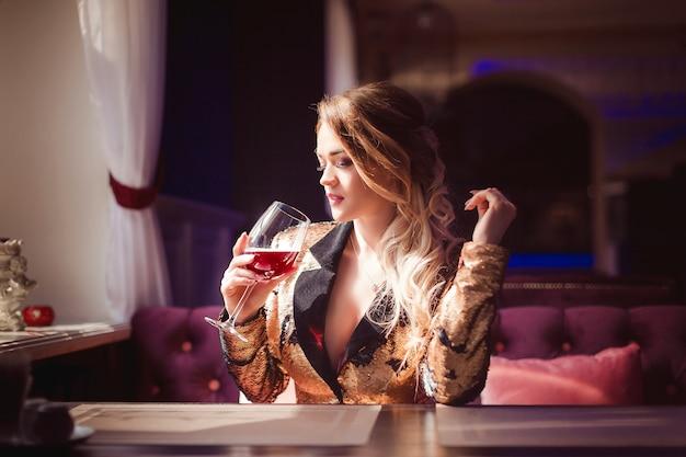 Linda mulher sensual em roupas elegantes, sentado no café, bebendo videira