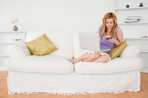 Linda mulher sentada em um sofá vai fazer um pagamento na internet enquanto está sentado em um sofá