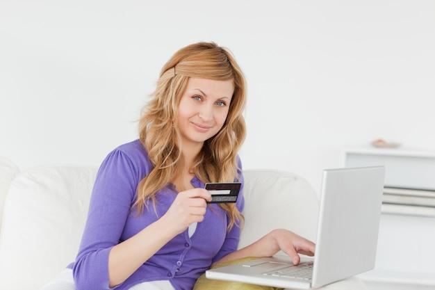 Linda mulher sentada em um sofá vai fazer um pagamento na internet