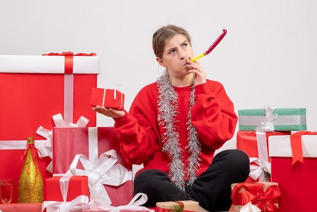 Linda mulher sentada em volta de presentes de natal em branco