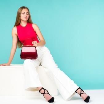 Linda mulher sentada no banco com bolsa vermelha e sapatos de salto alto.