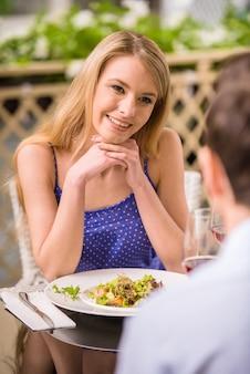 Linda mulher sentada no restaurante com o namorado.