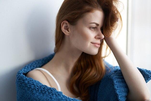 Linda mulher sentada perto da janela com uma manta azul de manhã. foto de alta qualidade