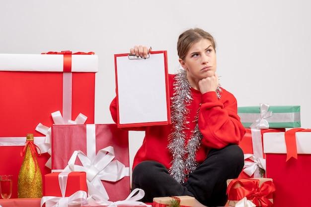 Linda mulher sentada perto de presentes de natal com nota em branco
