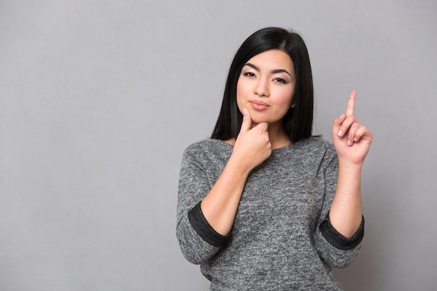Linda mulher séria com um macacão cinza apontando para cima com um dedo e tendo uma ideia