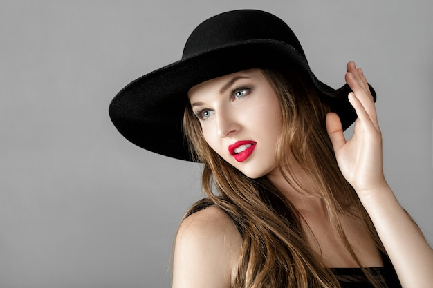 Linda mulher sexy com batom vermelho e chapéu preto