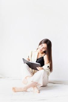 Linda mulher sexy com roupas confortáveis para casa escrevendo notas sentado no chão, pensando
