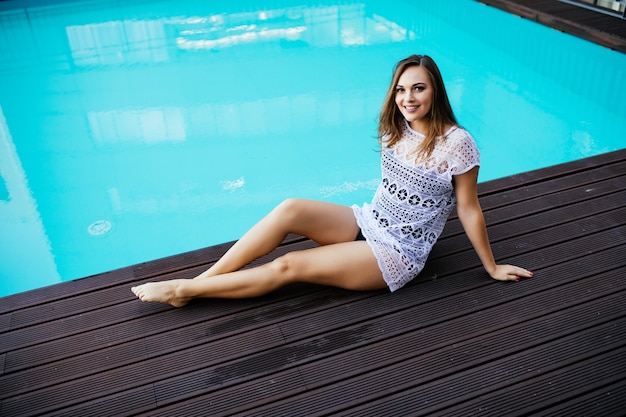 Linda mulher sexy deitada na beira da piscina, tomando banho de sol e relaxando na piscina na cobertura