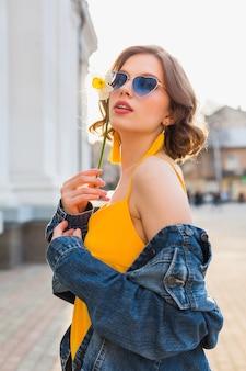 Linda mulher sexy e elegante em um vestido amarelo elegante usando jaqueta jeans, roupa da moda, tendência da moda primavera-verão, sol, óculos de sol azuis, moda de rua, estilo moderno, acessórios de moda