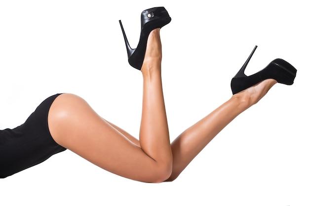 Linda mulher sexy e longa pernas para cima com calcanhares e meia-calça em um fundo branco isolado