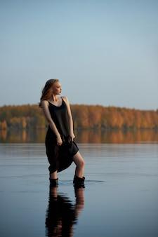 Linda mulher sexy fica na água perto da lagoa sob os raios do sol poente