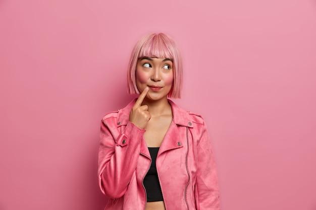 Linda mulher sonhadora asiática desvia o olhar com expressão pensativa, mantém o dedo perto da boca, vestida com roupa da moda tem penteado da moda cabelo rosa
