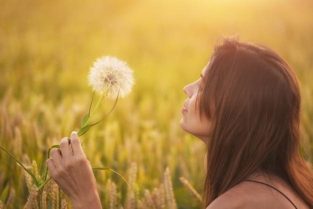 Linda mulher sopra dente de leão em um campo de trigo no pôr do sol de verão