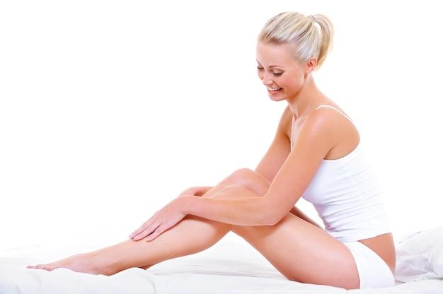 Linda mulher sorridente acariciando suas belas pernas, sentada na cama branca