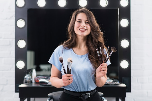 Linda mulher sorridente artista de maquiagem com pincéis nas mãos