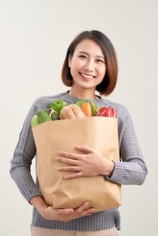 Linda mulher sorridente asiática segurando uma sacola de papel cheia de vegetais e mantimentos, estúdio tiro isolado no fundo branco
