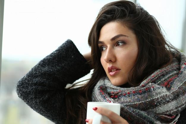 Linda mulher sorridente bebendo chá no inverno